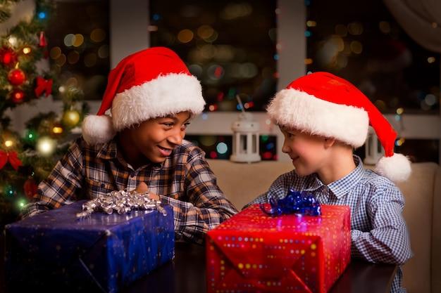 Dwoje dzieci w pobliżu prezentów świątecznych.