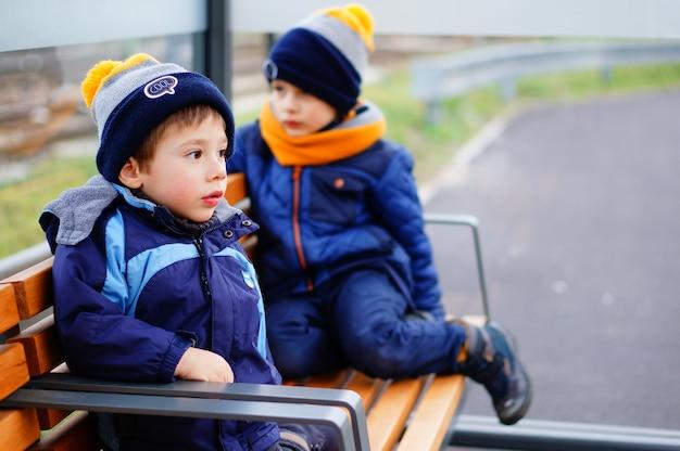 Dwoje dzieci w zimowe ubrania siedzi na ławce