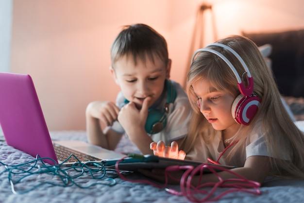 Dwoje dzieci z laptopa i tabletu na łóżku