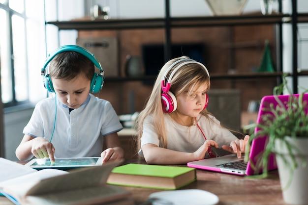 Dwoje dzieci z laptopem i tabletem