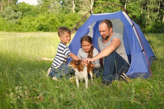 Dwoje dzieci z ojcem bawi się z psem chihuahua w namiocie w przyrodzie. kemping rodzinny. szczęśliwa rodzinna wycieczka latem. miłość rodzeństwa. podróżuj ze zwierzętami