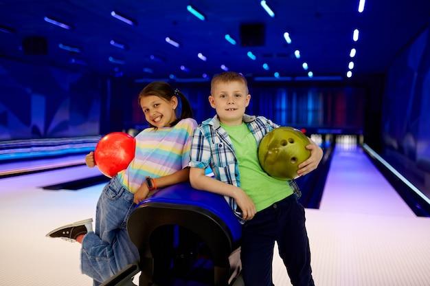 Dwoje dzieci z piłkami pozuje w kręgielni