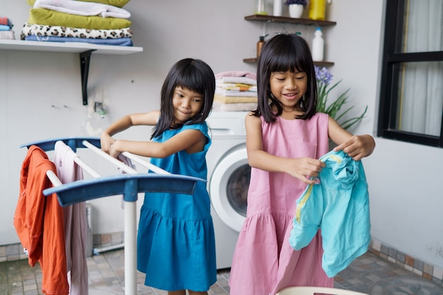 Dwoje dzieci zabawy szczęśliwa mała dziewczynka do prania ubrań i śmieje się w pralni