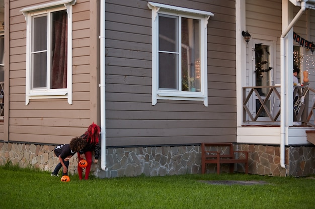Dwoje dzieci zakradających się do domu na halloween