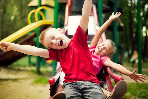 Dwoje dzieci zjeżdża na placu zabaw