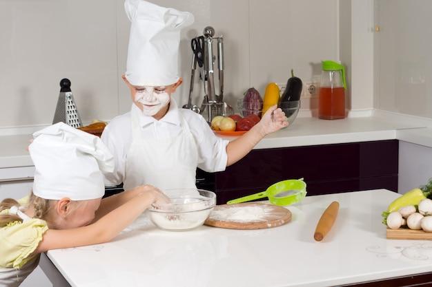 Dwoje głupich dzieciaków w kuchni bawi się mąką