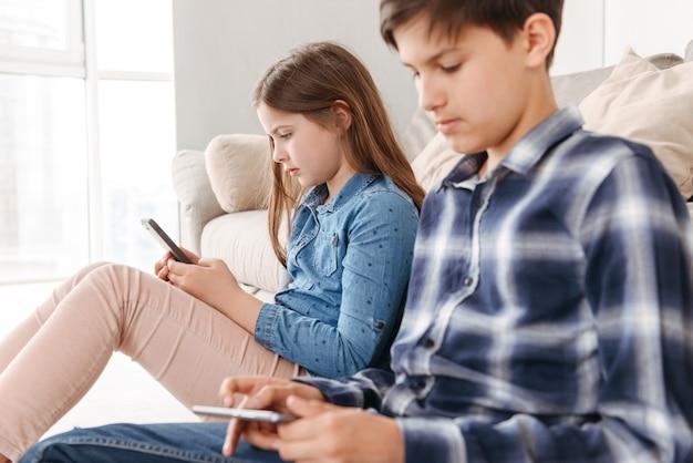 Dwoje kaukaskich dzieci, dziewczyna i chłopiec, siedząc na podłodze w pobliżu sofy w domu i oboje za pomocą telefonu komórkowego