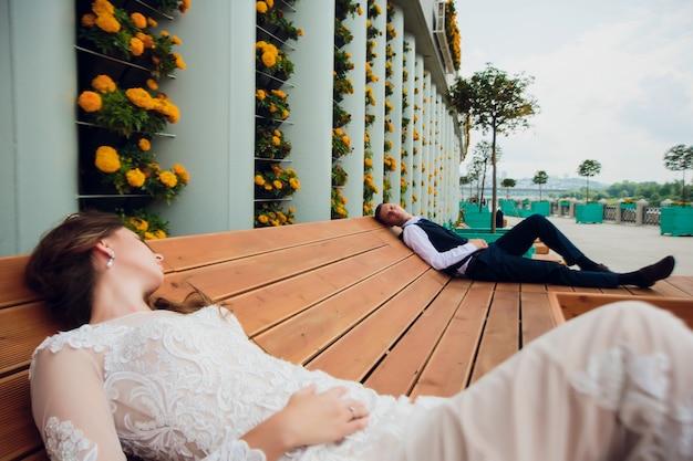 Dwoje kochanków siedzi na ławce, nowożeńcy kucają, by odpocząć w swoich ramionach podczas ślubnej sesji zdjęciowej, panna młoda w białej sukni i pan młody w pięknym garniturze na emeryturze w parku.