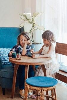 Dwoje mądrych dzieci siedzi razem przy stole i maluje na tablecie cyfrowym ołówkiem w nowoczesnym salonie.