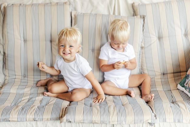 Dwoje małych bliźniaków. dwa identyczne niemowlęta w białych ubraniach dla dzieci siedzą na sofie w ciepłym domu i trzymają w dłoni ciastko. spontaniczny portret bliźniaków o niebieskich oczach i blond włosach
