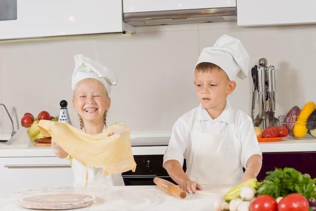 Dwoje małych dzieci bawi się przy robieniu pizzy?