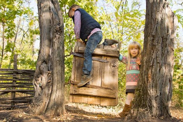Dwoje małych dzieci bawiących się na starej drewnianej bramie na zewnątrz w lesie z małym chłopcem wiszącym na niej, obserwowanym przez uśmiechniętą blondynkę