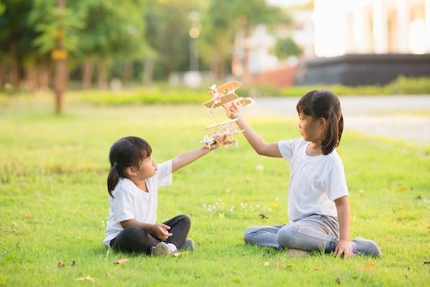 Dwoje małych dzieci bawiących się tekturowym samolocikiem w parku w ciągu dnia