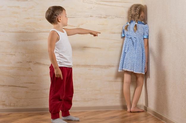 Dwoje małych dzieci bawiących się w domu, gdy rodziców nie ma, na białym tle na drewnianych ścianach