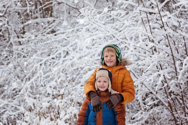 Dwoje małych dzieci, bracia chłopiec bawi się na zewnątrz podczas opadów śniegu. aktywny wypoczynek z dziećmi zimą w chłodne dni.