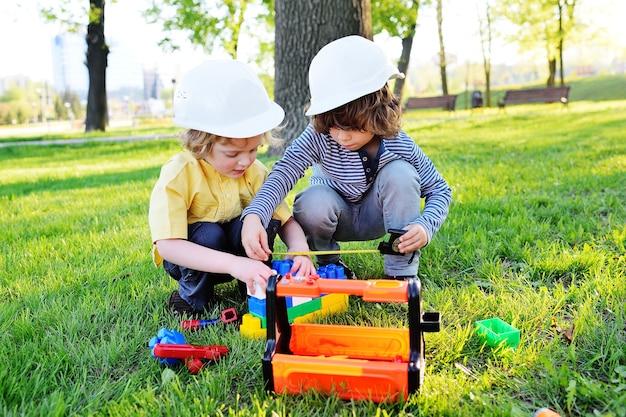 Dwoje małych dzieci chłopców w białych hełmach budowlanych bawi się w robotnikach zabawkowymi narzędziami.