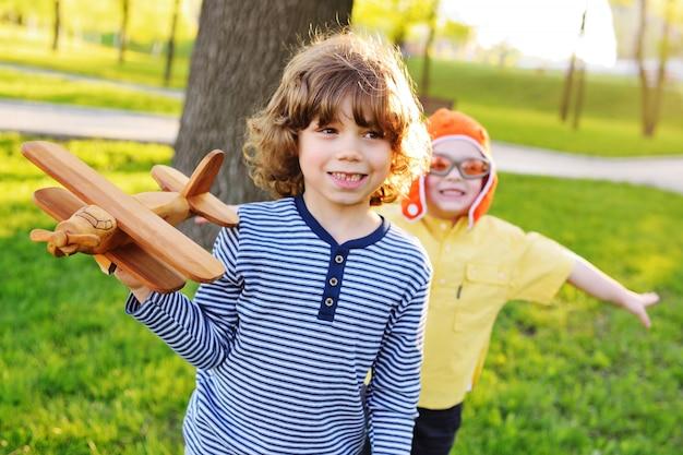 Dwoje małych dzieci chłopców z kręconymi włosami gra w parku drewniany samolot z zabawkami.