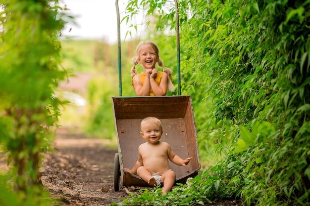 Dwoje małych dzieci dziewczynka i chłopiec na wsi w taczce ogrodowej siedzi uśmiechnięty