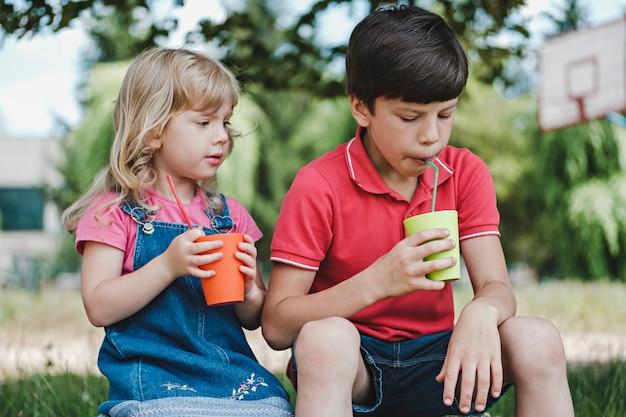 Dwoje małych dzieci przy zdrowym drinku
