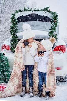 Dwoje małych dzieci w zimowym lesie pije gorący napój z kocem na ramionach