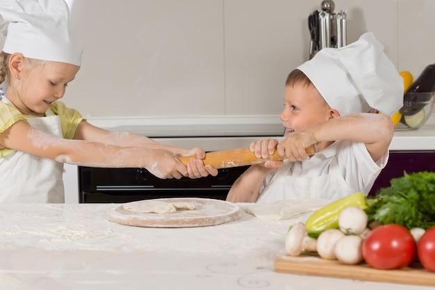 Dwoje małych dzieci walczy o wałek do ciasta