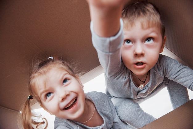 Dwoje małych dzieciaków chłopiec i dziewczynka otwierających karton i wspinających się na jego środku. dzieci bawią się dobrze