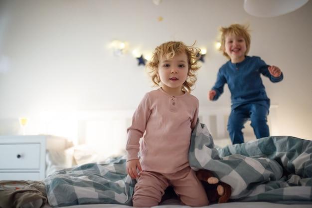 Dwoje małych roześmianych dzieci skaczących na łóżku w domu, bawiących się.