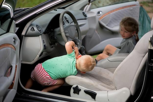 Dwoje małych uroczych dzieci - brat i siostra bawiący się w samochodzie za kierownicą.