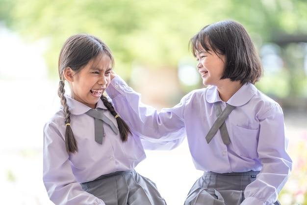Dwoje przyjaciół studentów dzieci wraca do szkoły i śmieje się z siebie. powrót do koncepcji szkoły stock photo