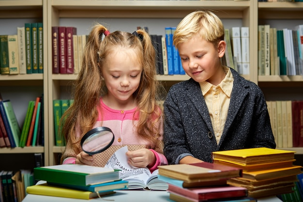 Dwoje przyjaznych dzieci w wieku szkolnym omawiających książkę podczas czytania w bibliotece, koncepcja edukacji. mózg dziecka, wiedza