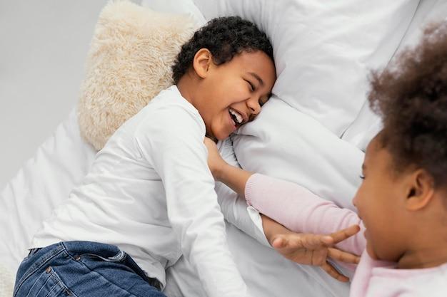 Dwoje rodzeństwa bawiące się w łóżku w domu