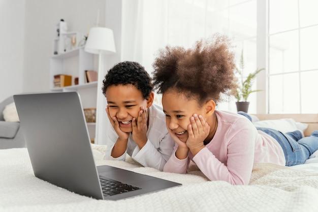 Dwoje rodzeństwa razem w domu grając na laptopie