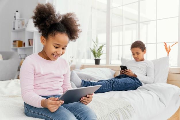 Dwoje rodzeństwa w domu razem grając na tablecie i smartfonie