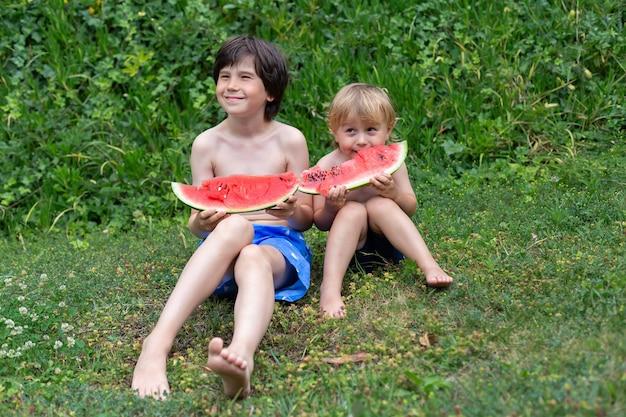 Dwoje rodzeństwa z dużymi czerwonymi kawałkami arbuza siedzi na zielonej trawie w letnim parku lub na placu zabaw. koncepcja pikniku obozu kidnergartnen