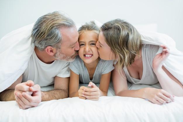 Dwoje rodziców leżących na łóżku i całujących córkę pod kocem