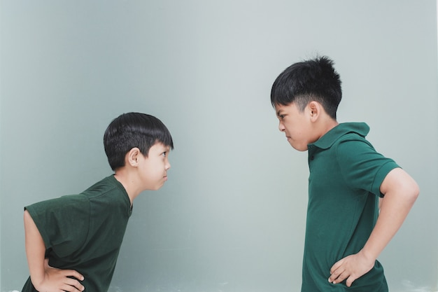 Dwoje rozzłoszczonych rodzeństwa patrzących na siebie na szarym tle