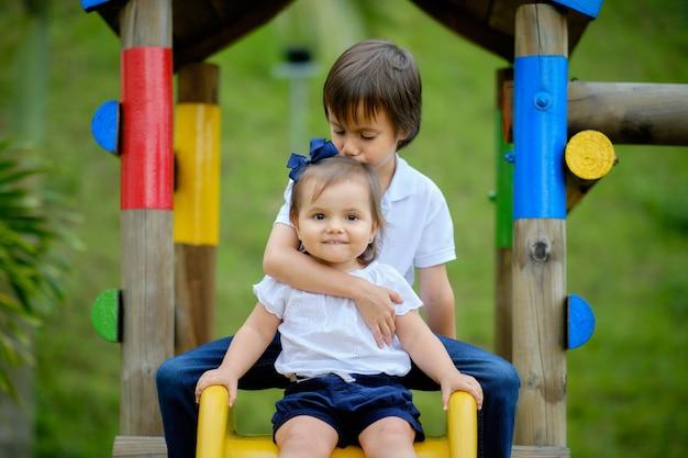 Dwoje szczęśliwego rodzeństwa, brat przytulający siostrę i całujący ją w głowę.
