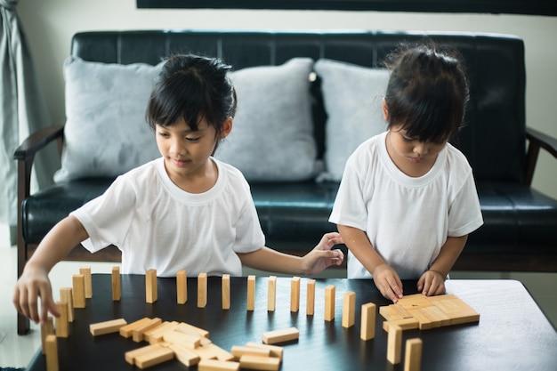 Dwoje szczęśliwego rodzeństwa radośnie bawi się w domu drewnianymi klockami