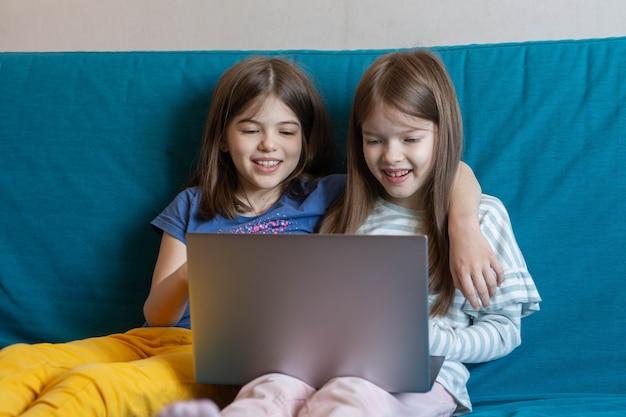 Dwoje szczęśliwych dzieci siedzi na kanapie i ogląda bajki na laptopie, grając w gry, ucząc się online na odległość, koncepcja e-learningu