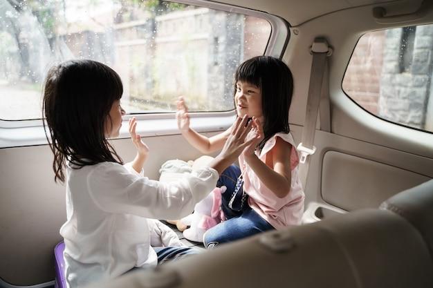 Dwoje szczęśliwych dzieci siedzi razem w bagażniku samochodu wesoła siostra grając razem w bagażniku pojazdu rodzinnego koncepcja podróży weekendowych i wakacji