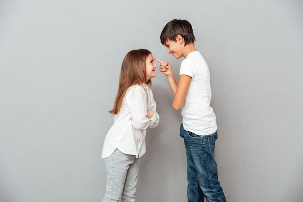 Dwoje szczęśliwych dzieci stojących i patrzących na siebie
