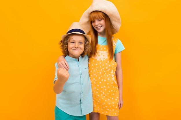 Dwoje szczęśliwych rudowłosych dzieci w kapeluszach