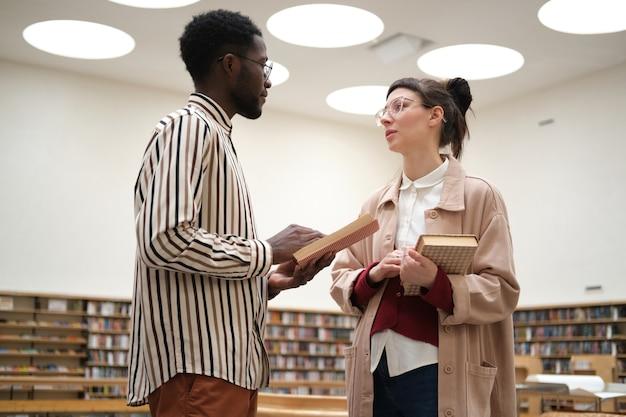 Dwoje uczniów rozmawiających o książkach i studiujących stojąc w bibliotece