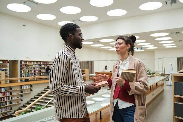 Dwoje uczniów trzymających książki i dyskutujących o czymś podczas nauki w bibliotece