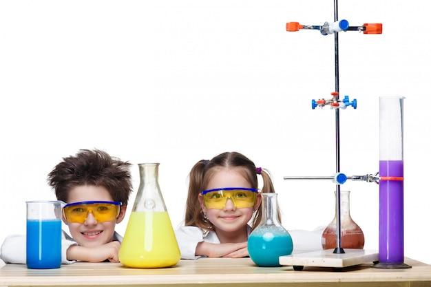 Dwoje uroczych dzieci podczas eksperymentów na lekcji chemii