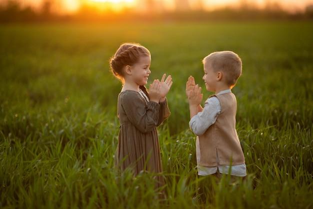 Dwoje wesołych bliźniaków, dziewczynka i chłopiec w rustykalnym ubraniu, bawią się i bawią o zachodzie słońca na polu zielonej młodej pszenicy.