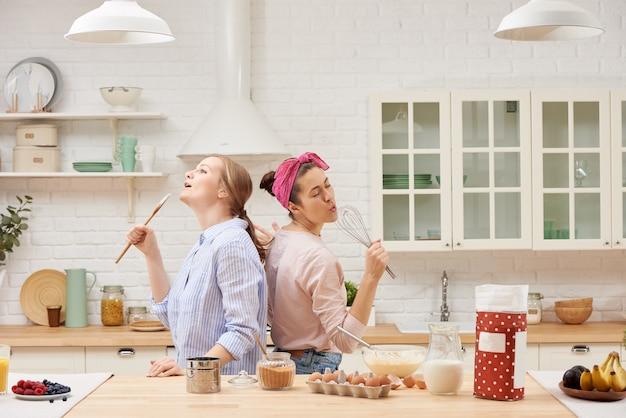Dwoje wesołych przyjaciół wspólnie gotuje desery i śpiewa