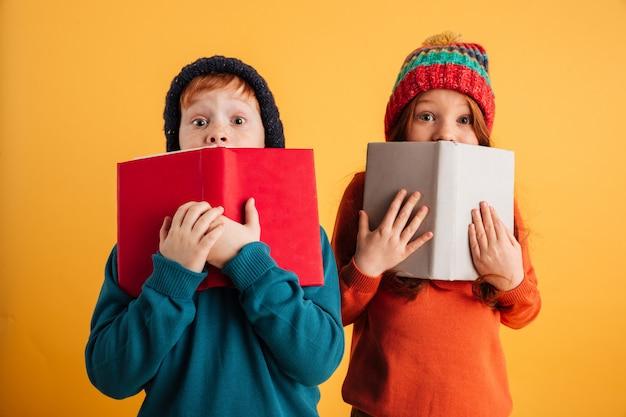 Dwoje wystraszonych małych rudych dzieci zakrywających twarze książkami.