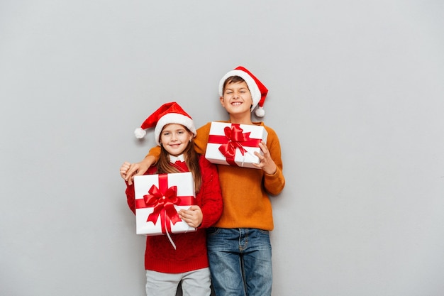 Dwoje zabawnych uroczych dzieci w czapkach świętego mikołaja z pudełkami na prezenty stojących razem