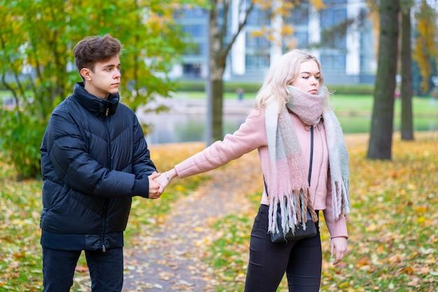 Dwoje zakochanych nastolatków w kłótni. blondynka obraża chłopca, facet trzyma ją za rękę,